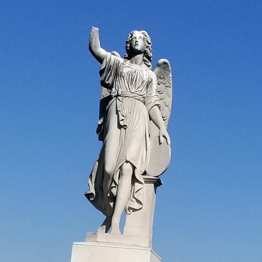 statue of an angel with a raised arm but missing hand