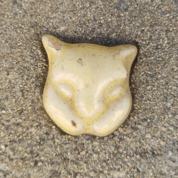 chipped yellow ceramic cat head embedded in cement