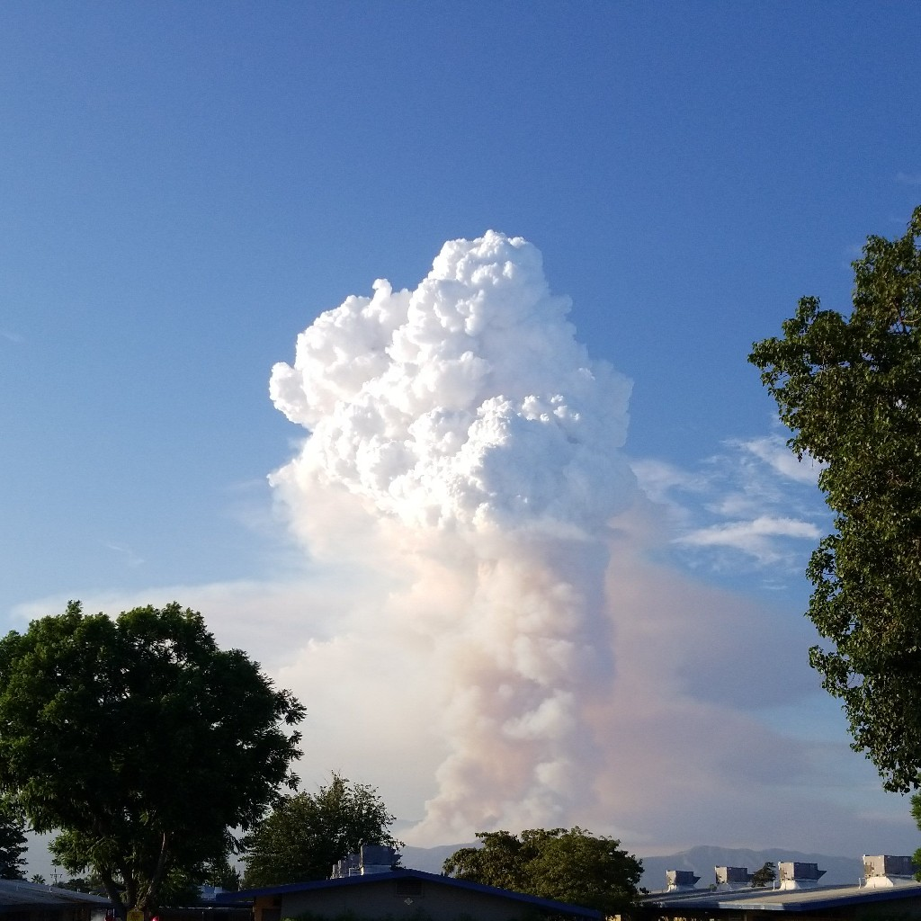 large plume of white and gray smoke rising from behind the mountain range in the distance