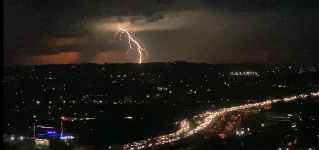 Dark image of city at night with freeway lights on lower right and lightning strike in the background